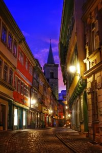 esrfurt sreet at dusk pink sky in the background behind the church tower narrow street in front of us